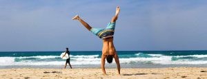 Surfer handstanding on the beach