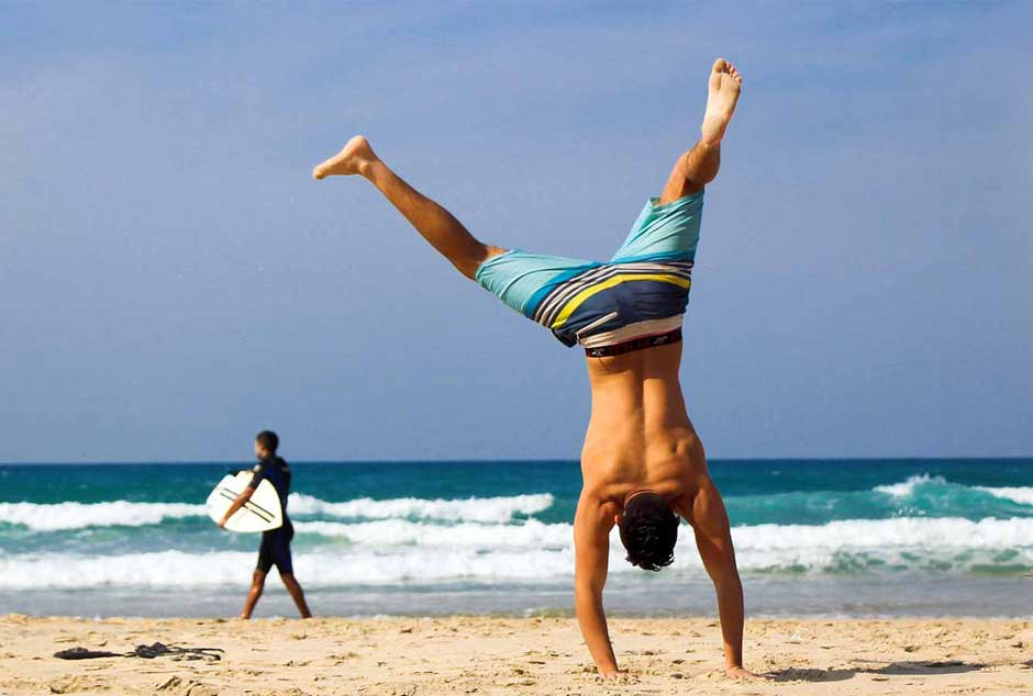 Surfer handstanding on the beach
